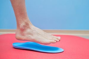 Foot hovering over foot orthotics.