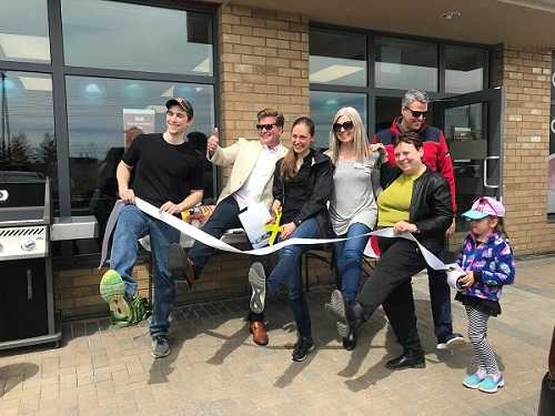 Owners of On the Ball Orthotics, City Councillor, Rainbows Representative, and two members from the chamber of commerce cutting the ribbon for the grand opening. All have one foot in the air