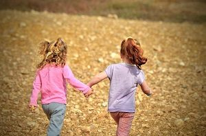 Two girls holding hands and running through a field of autumn leaves.