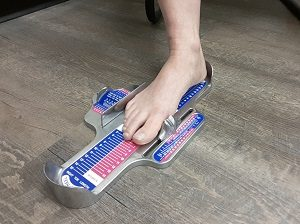 Right foot getting measured on a brannock device to determine the proper shoe size.