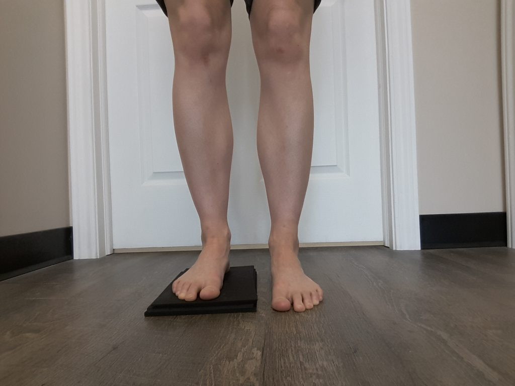 A block is placed under the right foot to depict a leg length discrepancy.