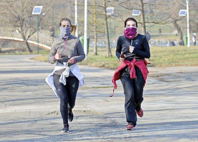 Two women running with masks on